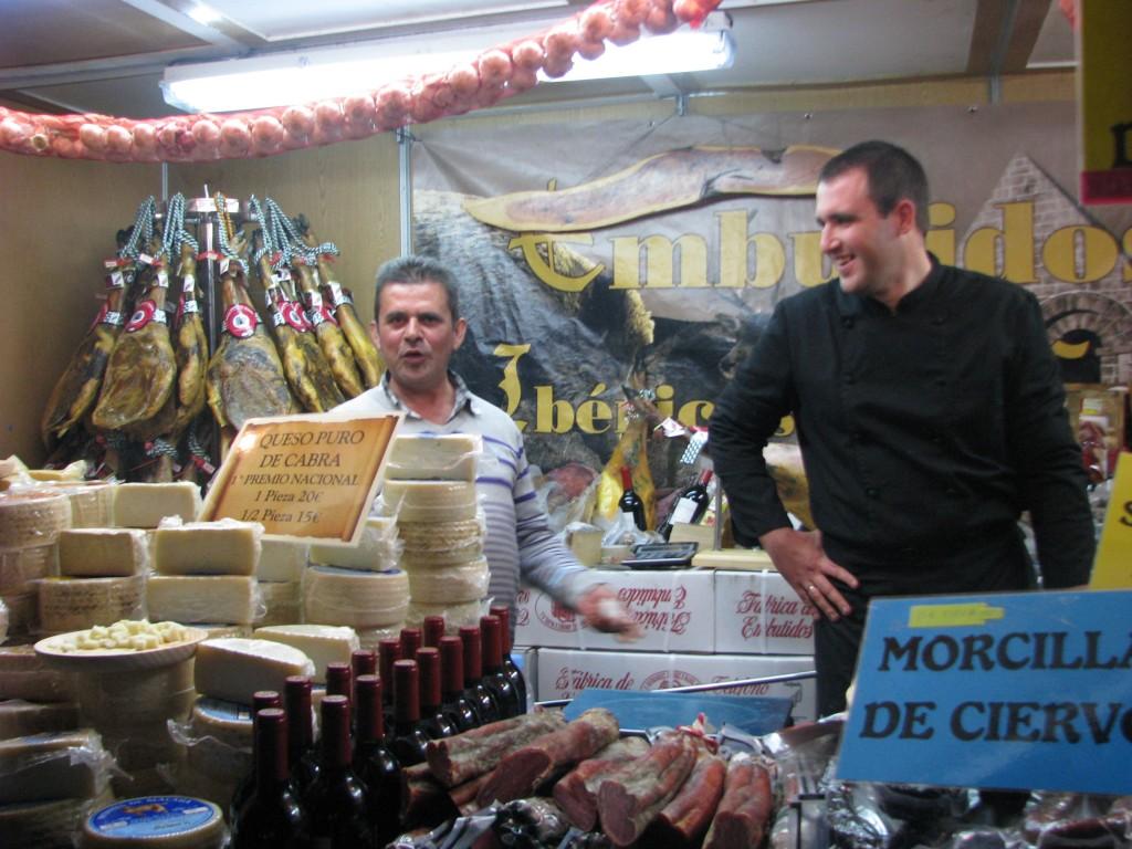 Stall selling morcilla (blood sausage), queso de cabra (goat cheese), and jamon Serrano (Iberian ham)